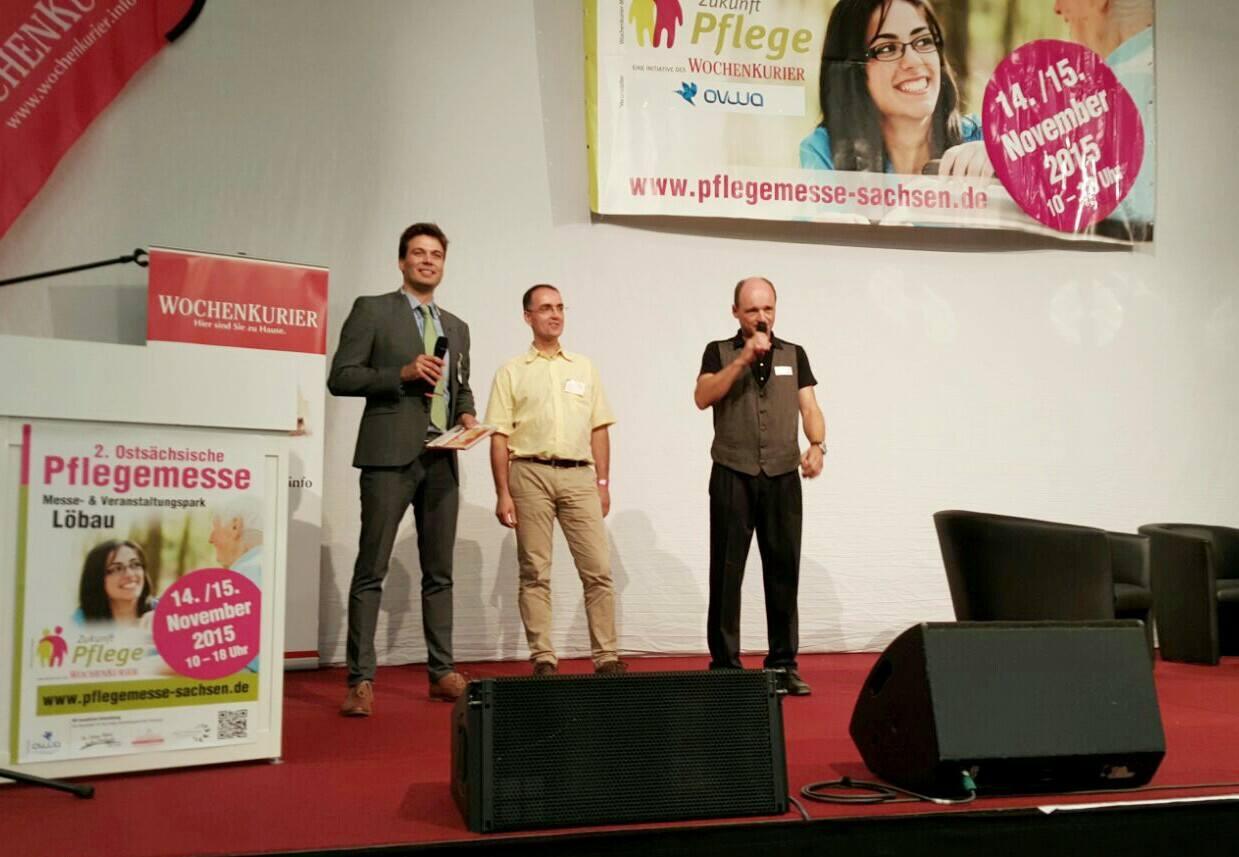 Herr Quaas auf großer Bühne (Mitte; Foto: CareSocial GmbH)